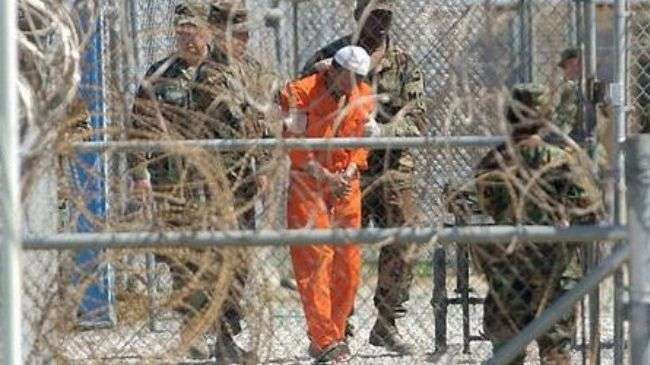 File photo shows a detainee with guards at the US-run prison camp in Guantanamo Bay, Cuba.