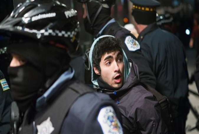 A demonstrator who was participating in a march calling for the resignation of Chicago Mayor Rahm Emanuel is taken into custody by the police in front of the Four Seasons Hotel on December 18, 2015 in Chicago, Illinois.