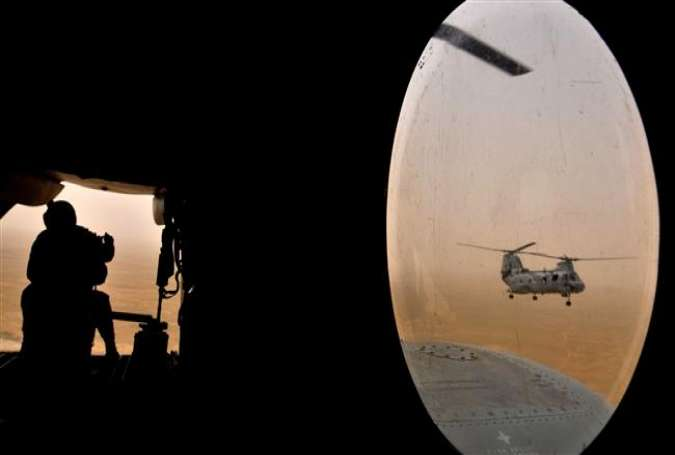 This AFP file photo taken on May 3, 2008 shows a US soldier (L) sitting in the rear of a Marine Chinook helicopter while flying over Camp Bastion in Helmand province, southwest of Kabul. (Photo by AFP)
