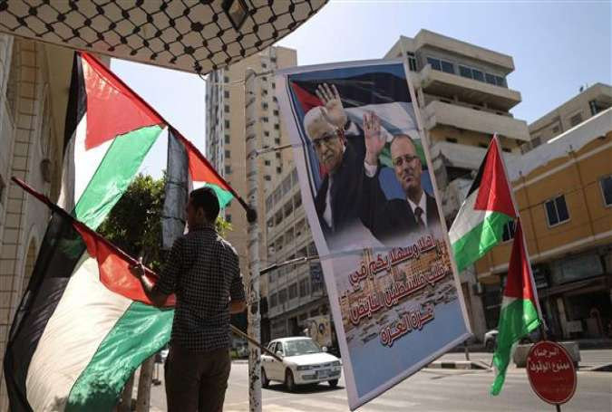 A Palestinian shop owner displays national flags and a poster bearing the portraits of Palestinian Prime Minister Rami Hamdallah and President Mahmoud Abbas on October 1, 2017, in the Gaza Strip. (Photo by AFP)
