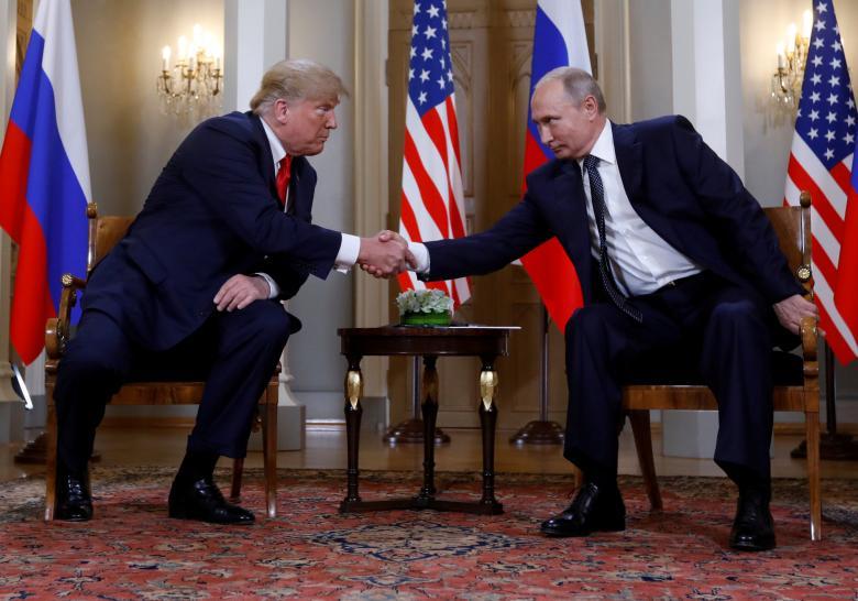 U.S. President Donald Trump and Russia's President Vladimir Putin shake hands as they meet.