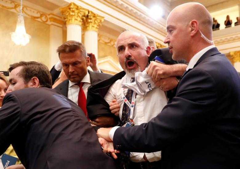 Security personnel removes a man from the premises before Trump and Putin's joint news conference.