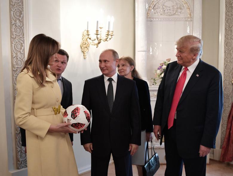 Russia's President Putin (C), U.S. President Donald Trump (R) and first lady Melania Trump speak during a meeting.