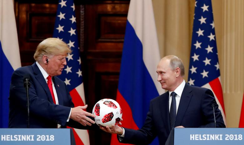 U.S. President Trump receives a football from Russian President Putin as they hold a joint news conference.