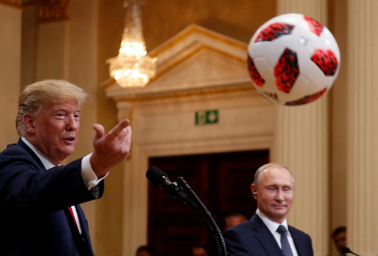 U.S. President Trump throws a football to first lady Melania Trump during a joint news conference.