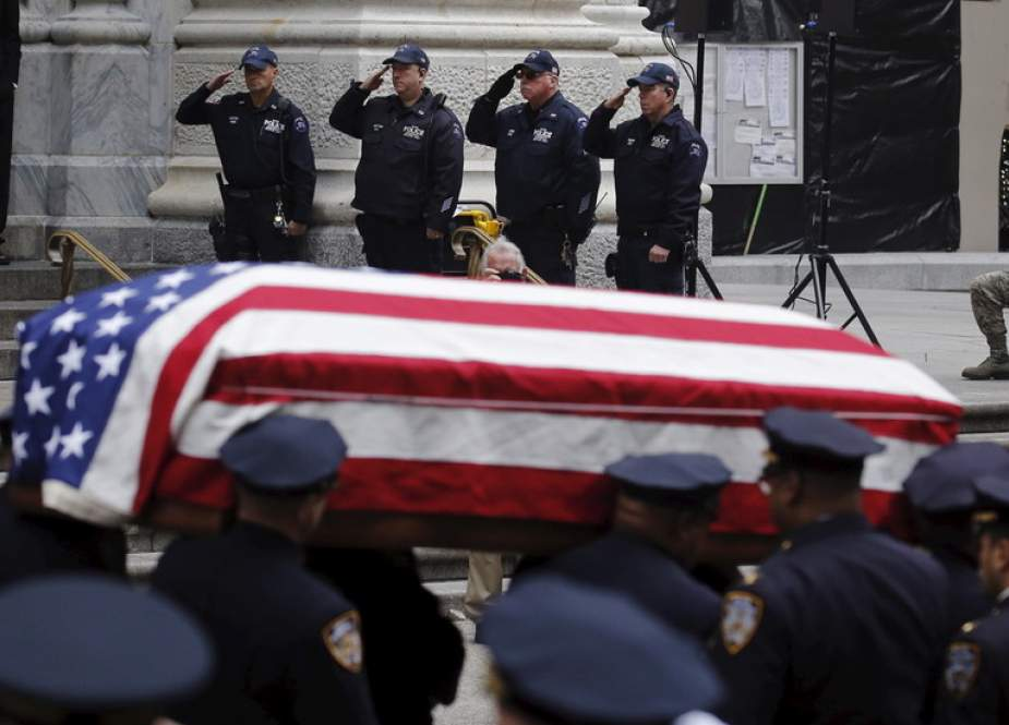 NYPD officers salute during the funeral.JPG