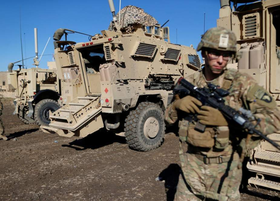 US soldiers stand next a military vehicle in the town of Bartella, Iraq.JPG